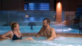 El par se relaja en una tina caliente al aire libre Mujer joven feliz y hombre que se relajan en agua caliente cerca de la piscin metrajes