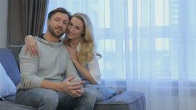 El par se sienta en el sofá en casa metrajes