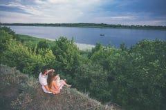 El par se sienta en la orilla del río foto de archivo libre de regalías