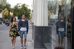El par sonríe y camina alrededor de la ciudad, y va a hacer compras, otoño y primavera imagen de archivo libre de regalías