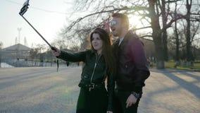 El par toma la foto en el artilugio móvil en el palillo del selfie, teléfono en el uno mismo-palillo, paseo elegante de la muchac metrajes