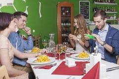 El par toma las fotos de sus comidas Imágenes de archivo libres de regalías
