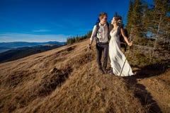 El par turístico de la boda sube en el top de la montaña honeymoon imagen de archivo libre de regalías