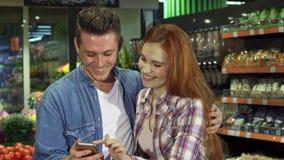 El par utiliza smartphone en el hipermercado almacen de video