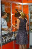 El para mujer joven de la joyería JUNWEX Moscú 2014 está eligiendo la joyería Foto de archivo libre de regalías