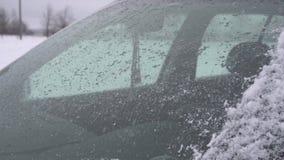 El parabrisas en invierno, limpiadores del coche del coche limpia el vidrio, nevada almacen de metraje de vídeo