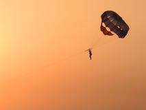 El paracaidista contra el cielo rojo Fotografía de archivo