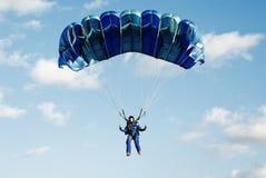 El paracaidista de la muchacha en guardapolvos azul marino Fotos de archivo libres de regalías