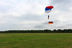 El paracaidista está aterrizando con la bandera alemana imagen de archivo
