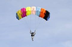 El paracaidista va abajo en un paracaídas multicolor Foto de archivo