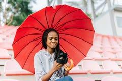 El paraguas afroamericano sonriente hermoso del und del adolescente está mandando un SMS vía el teléfono móvil en el estadio Imagenes de archivo