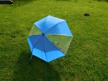 El paraguas azul en jardín con topera Foto de archivo