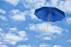 El paraguas azul vuela en cielo contra de las nubes blancas Viento de chang Imagen de archivo