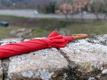 el paraguas rojo encendido remata una pared Foto de archivo libre de regalías
