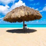 El paraguas y la playa acuestan en una playa del Caribe Foto de archivo
