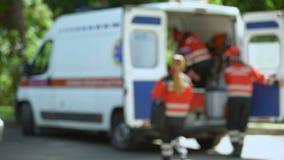 El paramédico mira la cámara, consiguiendo en la ambulancia, el transporte del paciente metrajes