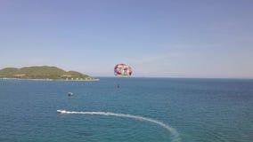 El parasail de la visión aérea que volaba sobre el mar azul tiró del barco El Parasailing en bahía del mar y la isla verde ajardi metrajes