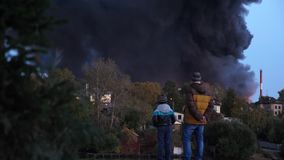El parecer de la gente una casa quema La tragedia, gente está mirando un fuego grande en la ciudad La aflicción de la gente quemó metrajes