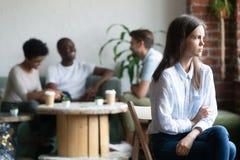 El paria de la muchacha se sienta aparte de pares en cafetería fotos de archivo