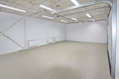 El parking vacío, almacena el interior con las puertas blancas grandes y el suelo de baldosas gris Foto de archivo