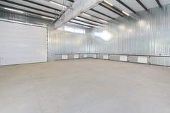 El parking vacío, almacena el interior con las puertas y las ventanas blancas grandes dentro imagen de archivo