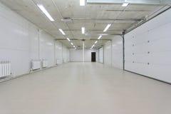 El parking vacío, almacena el interior con las puertas y las ventanas blancas grandes dentro foto de archivo libre de regalías