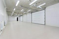El parking vacío, almacena el interior con las puertas y las ventanas blancas grandes dentro imagen de archivo libre de regalías