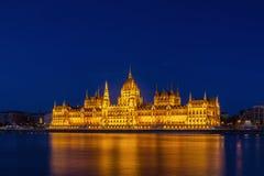 El parlamento húngaro iluminado en el Danubio Foto de archivo