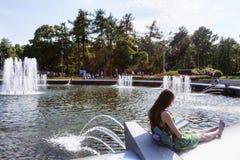El parque de Sokolniki, mujer lee el libro al borde de la fuente, ella disfruta del día de verano de marinos del ejército de la m Imagenes de archivo
