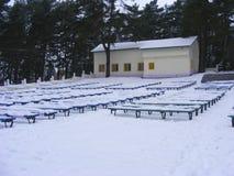 El parque del invierno de la ciudad con una fila de la nieve benches, sanatorio en invierno, benchs cubiertos con nieve fotos de archivo