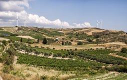 El parque eólico y la aceituna colocan con el cielo azul y las nubes en la isla de Creta, Grecia fotos de archivo
