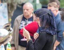 El participante del festival en el traje de una señora medieval intenta encendido una cadena y considera en un espejo el ingenio  imagenes de archivo