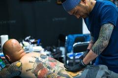 El participante del festival hace tatuajes en el 11mo convenio internacional del tatuaje en el centro de la Congreso-EXPO de Krak Imágenes de archivo libres de regalías