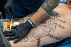 El participante del festival hace tatuajes en el 11mo convenio internacional del tatuaje en el centro de la Congreso-EXPO de Krak Fotos de archivo