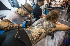 El participante del festival hace tatuajes en el 11mo convenio internacional del tatuaje en el centro de la Congreso-EXPO de Krak Fotografía de archivo libre de regalías