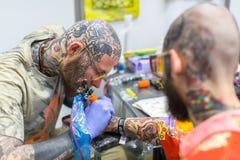 El participante del festival hace tatuajes en el 11mo convenio internacional del tatuaje en el centro de la Congreso-EXPO de Krak Fotos de archivo libres de regalías