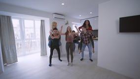 El partido casero, los amigos divertidos jovenes juega la raza en el apartamento que los muchachos fuertes felices están llevand almacen de video