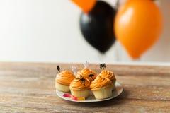El partido de Halloween adornó las magdalenas en la placa Foto de archivo
