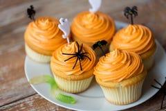 El partido de Halloween adornó las magdalenas en la placa Imagenes de archivo