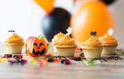 El partido de Halloween adornó las magdalenas en la tabla de madera Imagen de archivo