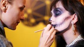 El partido de Halloween, artista de maquillaje dibuja un maquillaje terrible en la cara de una mujer morena para un partido de Ha almacen de metraje de vídeo
