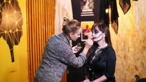 El partido de Halloween, artista de maquillaje dibuja un maquillaje terrible en la cara de una mujer morena para un partido de Ha almacen de video