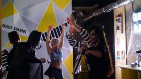 El partido de Halloween, disco, gente joven está bailando, todo el mundo se viste en los trajes asustadizos para Halloween En el  almacen de video