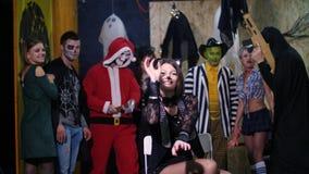 El partido de Halloween, sesión de foto, gente joven se vistió para arriba en trajes asustadizos e hizo un maquillaje espantoso e almacen de metraje de vídeo