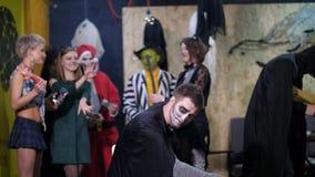 El partido de Halloween, sesión de foto, gente joven se vistió para arriba en trajes asustadizos e hizo un maquillaje espantoso e almacen de video