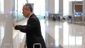 El pasajero del hombre de negocios del pasajero en el escritorio del incorporar del aeropuerto, recibe un boleto del vuelo almacen de video
