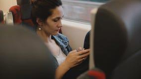 El pasajero femenino casual en el tren se sienta en un asiento cómodo usando el comercio electrónico app del smartphone, mirando  almacen de video