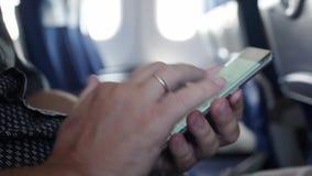 El pasajero utiliza smartphone en el avión Ciérrese para arriba de sus manos 1920x1080 metrajes