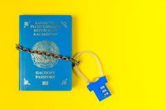 El pasaporte de Kazajistán se envuelve en la cadena cerrada en la cerradura Fotos de archivo