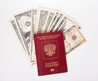 El pasaporte ruso miente en una pila de notas (los dólares) Imagen de archivo libre de regalías